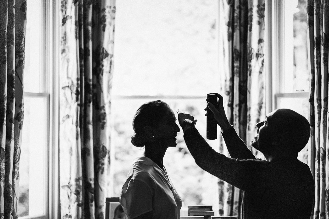 a bride putting finishing touches to her hair pre wedding ceremony