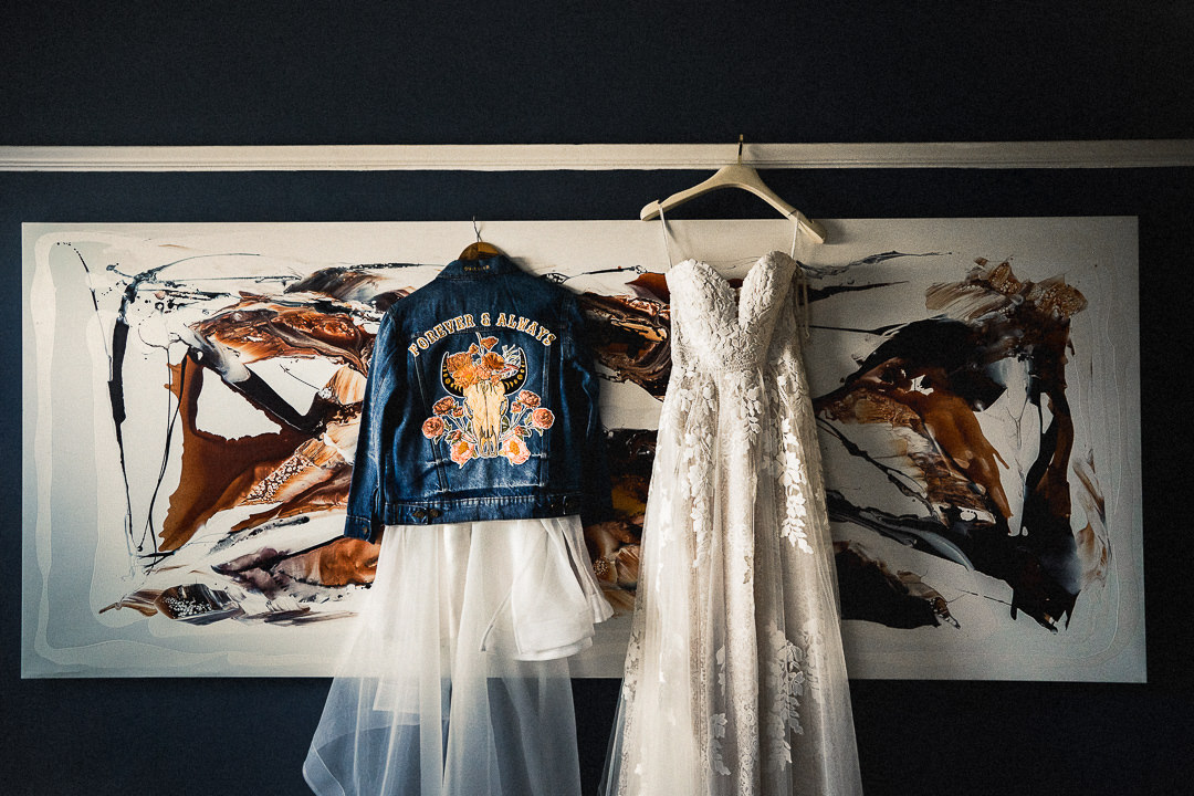 2 bridal dresses and a bespoke denim jacket hanging at the brides home pre wedding ceremony in London