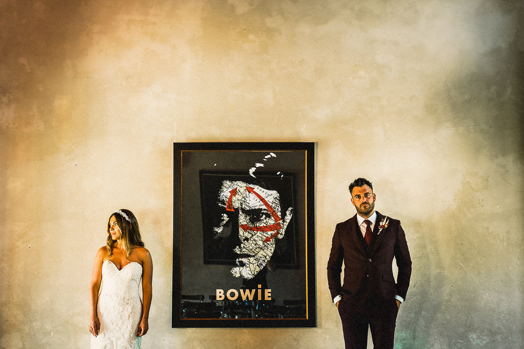 a wedding couple stand either side of a David bowie poster at the eclectic voewood wedding venue in Norfolk