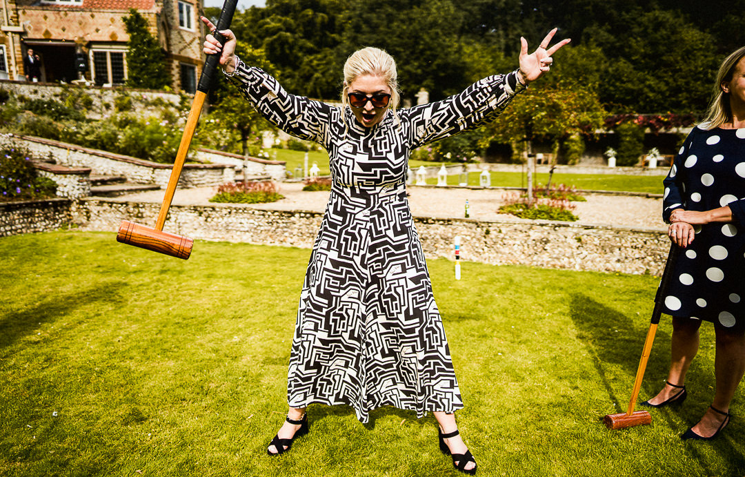 wedding guest celebrates in bold print dress during lawn games