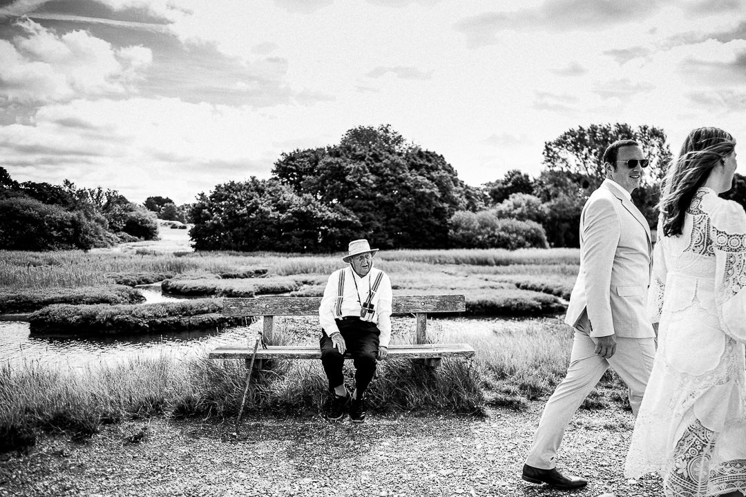 a local pensioner looks confused as a young couple walk past his favourite seaside bench ahead of catching a ferry to their awaiting guests and wedding ceremony.