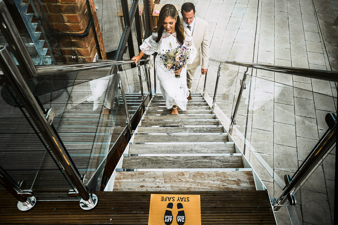 A bride and groom climb the stairs leading to the balcony they will have their wedding ceremony. A Covid safety sticker in shot to add context