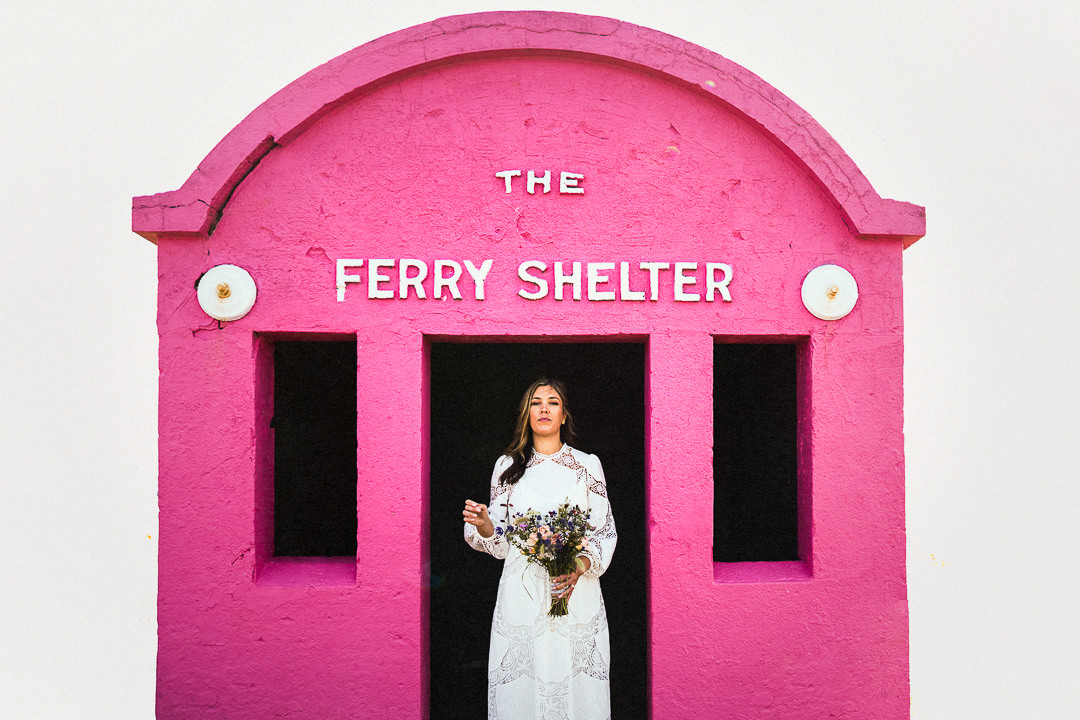 A bride in a white dress stands in the entrance of a bright pink ferry shelter before her micro wedding