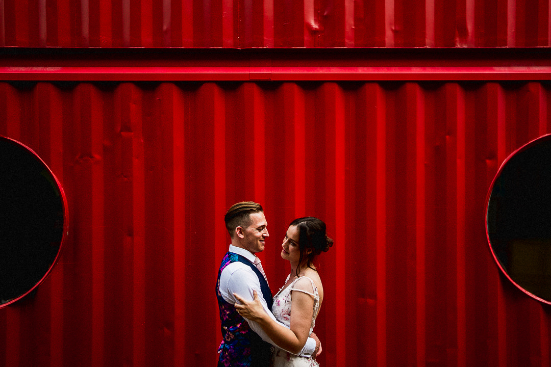 A couple embracing in front of a dark red shipping container on their wedding day at trinity buoy wharf