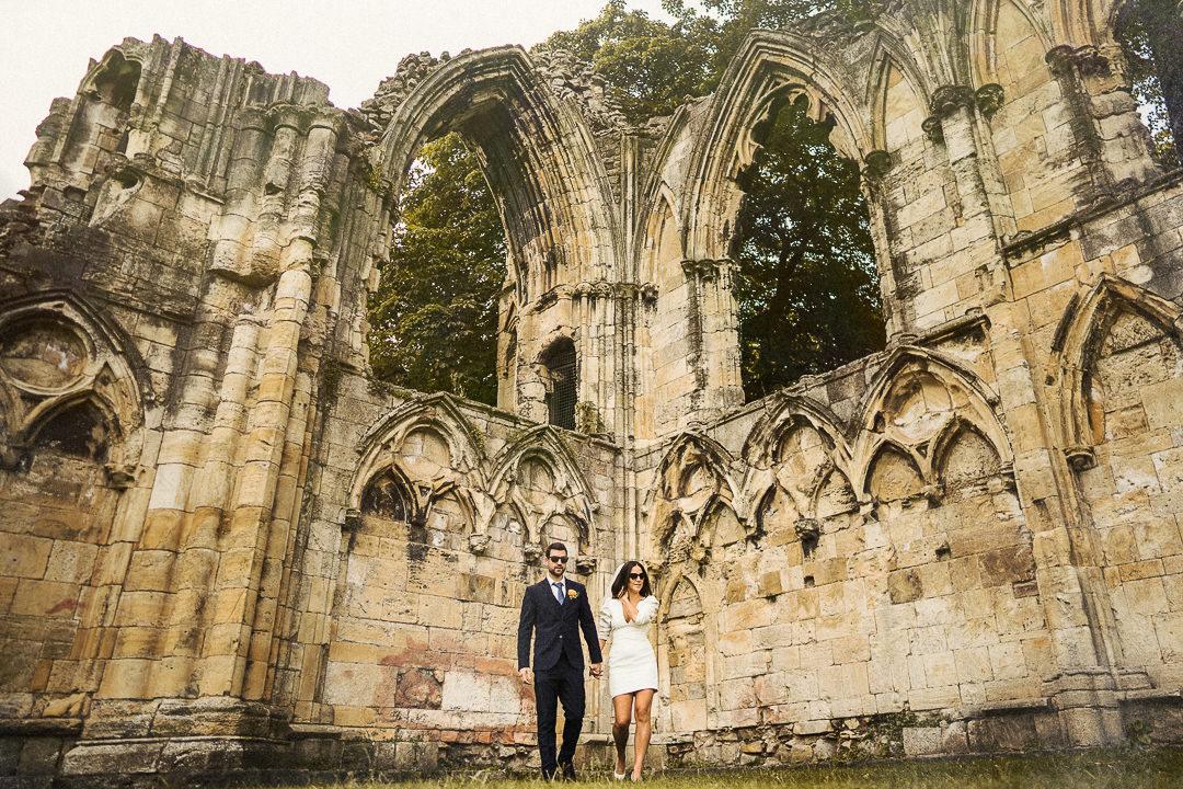 a wedding couple walk away from some ancient ruins in York after their elopement