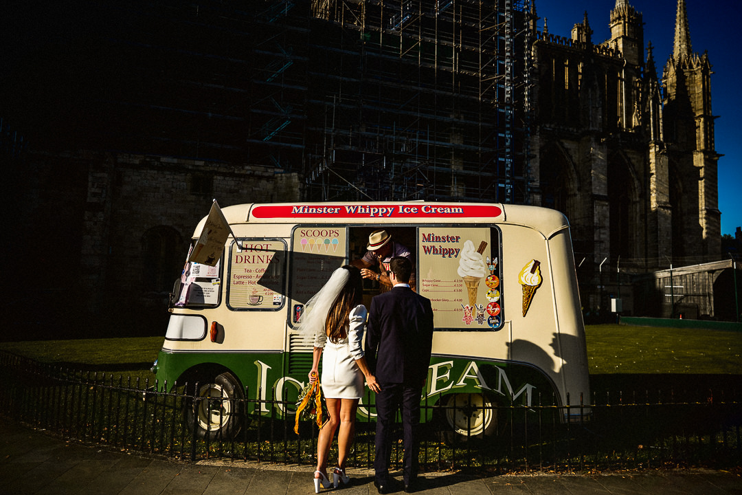a wedding couple order and ice-cream in front of York minster after eloping