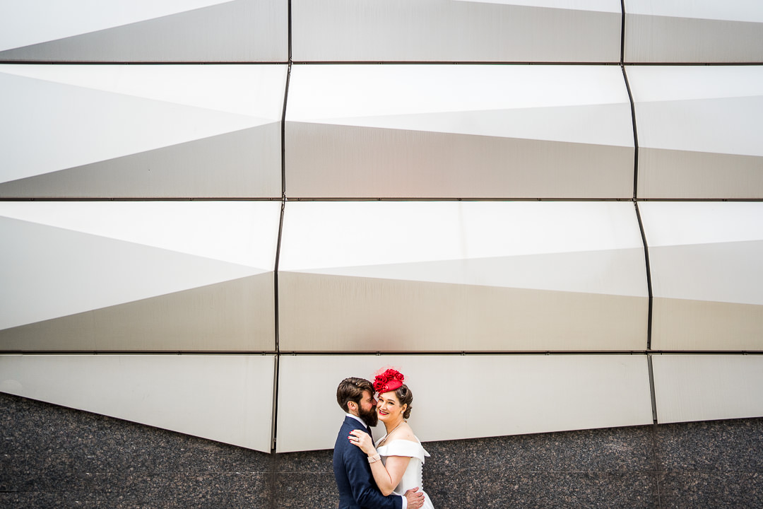 A bride in red hat embraces her groom outside a reflective building in Marylebone