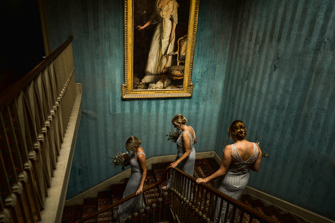 3 bridesmaids walk down the stairs ahead of a Dorset wedding ceremony