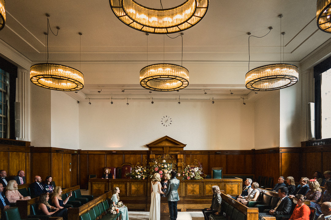 a wide shot of a ceremony in the council chamber at The Town Hall Hotel in London