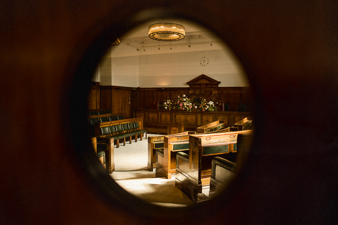 a view of the town hall hotels ceremony room shot through a port hole window
