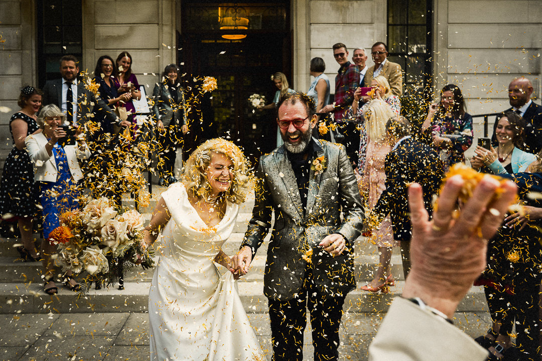 orange confetti being thrown at a wedding couple outside the downhill hotel in East London