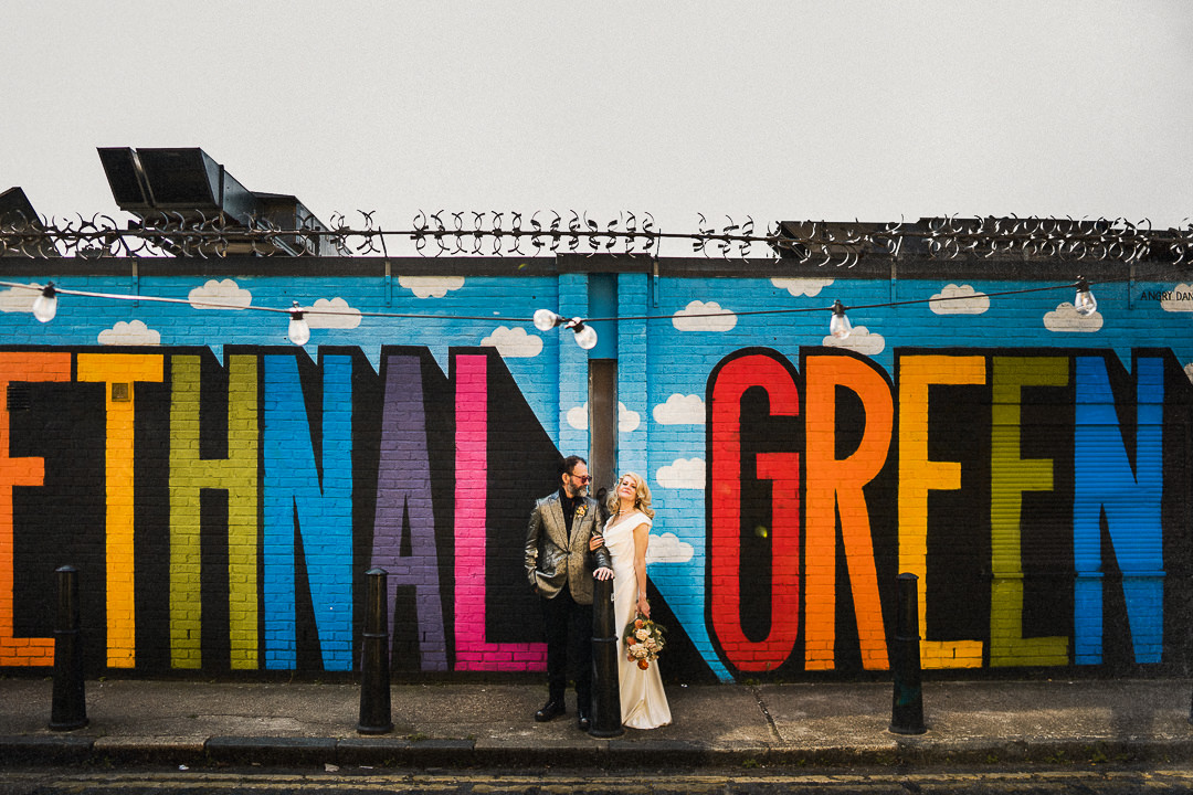 a wedding couple stand in front of a colourful art installation in Bethnal Green
