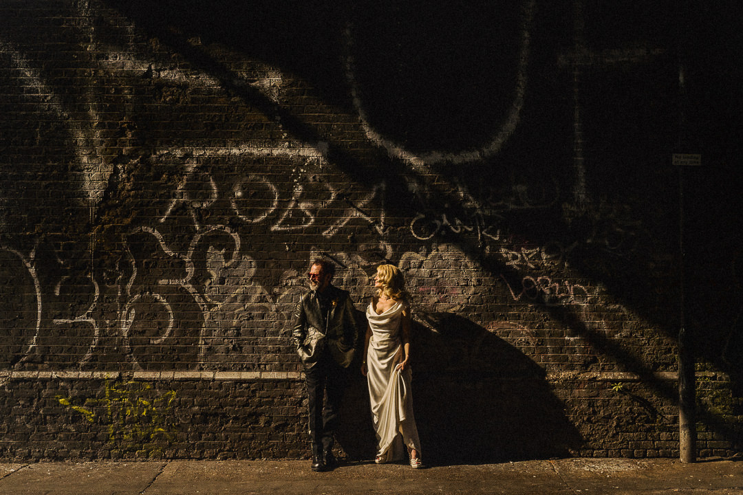 A couple stand beneath a railway bridge in East London on their wedding day