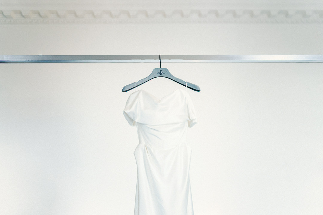 A Vivienne Westwood dress hanging in a bridal suite against a clean white backdrop