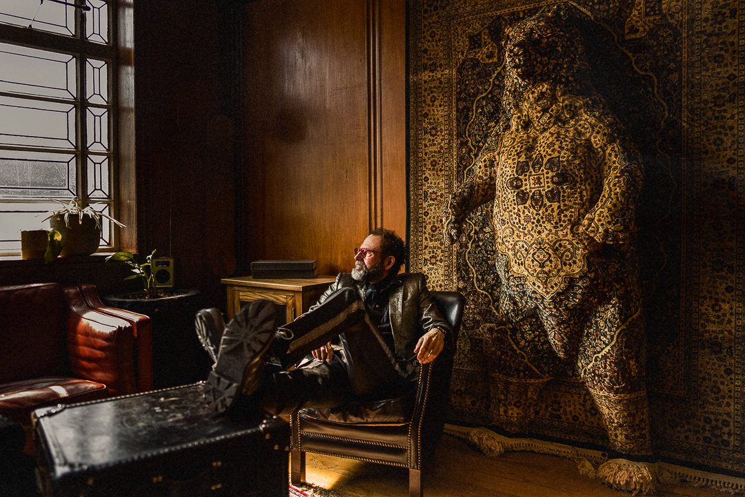 a groom sits in front of a sculpted bear at the downhill hotel in Bethnal Green