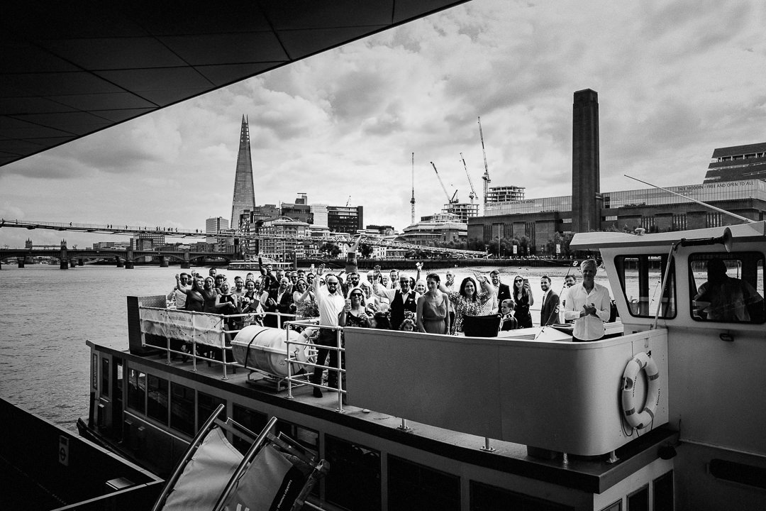 waving wedding guest aboard a passenger party boat on the thames at Blackfriars