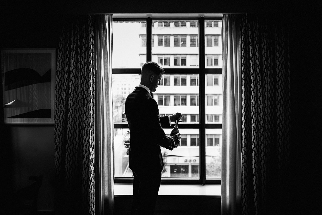 a wedding groom opens a bottle of Prosecco at the Hoxton hotel