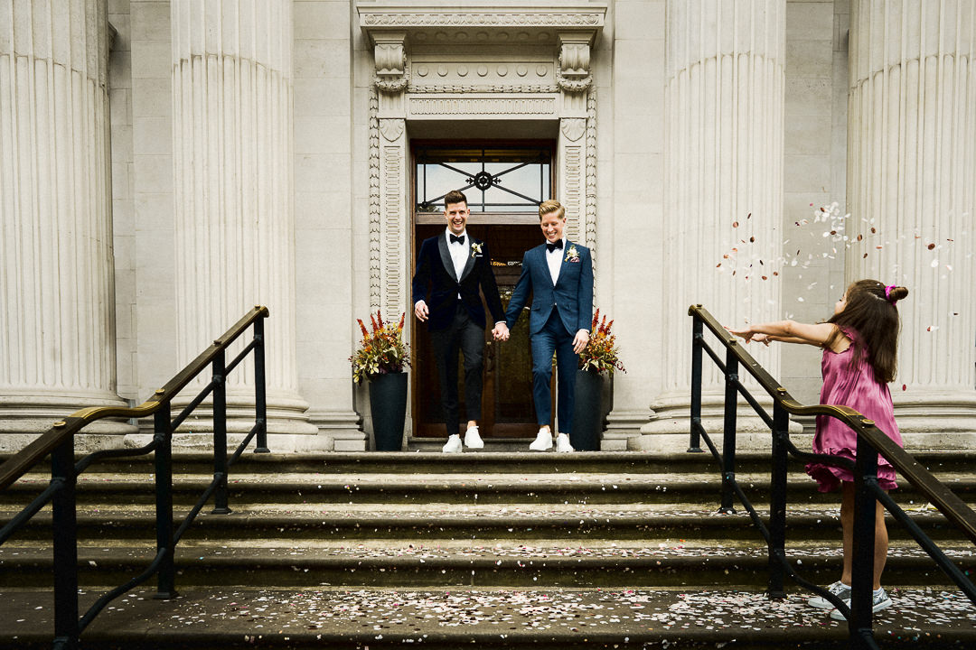 a same sex couple exit Marylebone town hall to steps covered in confetti