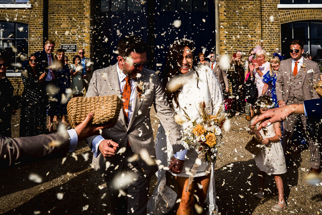 a bride and groom covered in confetti after their wedding at trinity buoy wharf