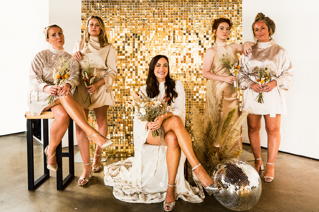 an alternative bridal party group shot including disco balls and pampas grass at trinity buoy