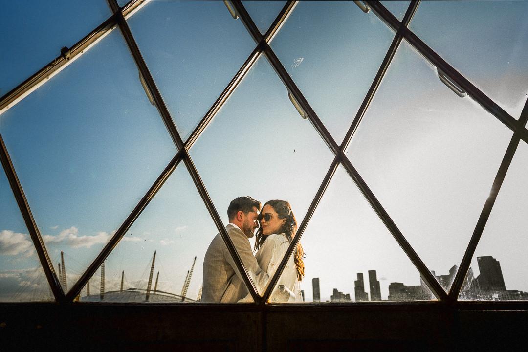 a wedding couple embrace on the balcony of trinity buoy wharfs lighthouse in London