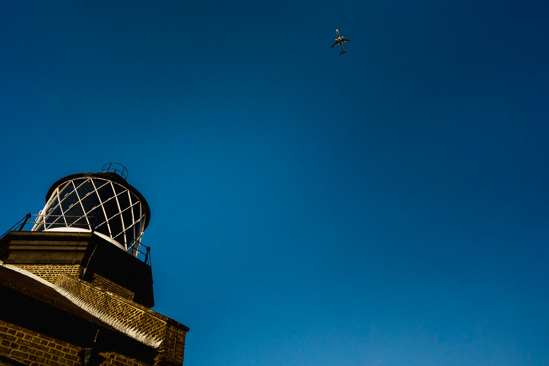 A plane flies through a clear blue sky in London above Trinity Buoy Wharf wedding venue