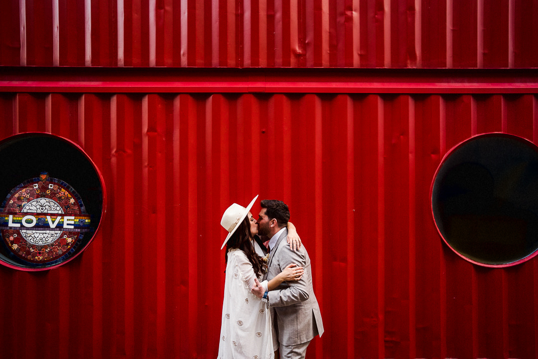 A cool wedding couple embrace against a red shipping container in Londons East End