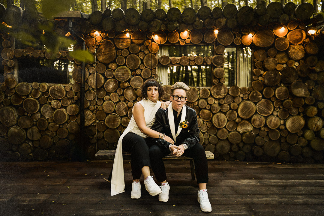 A same sex couple sit for a wedding portrait outside a log cabin at the dreys wedding venue