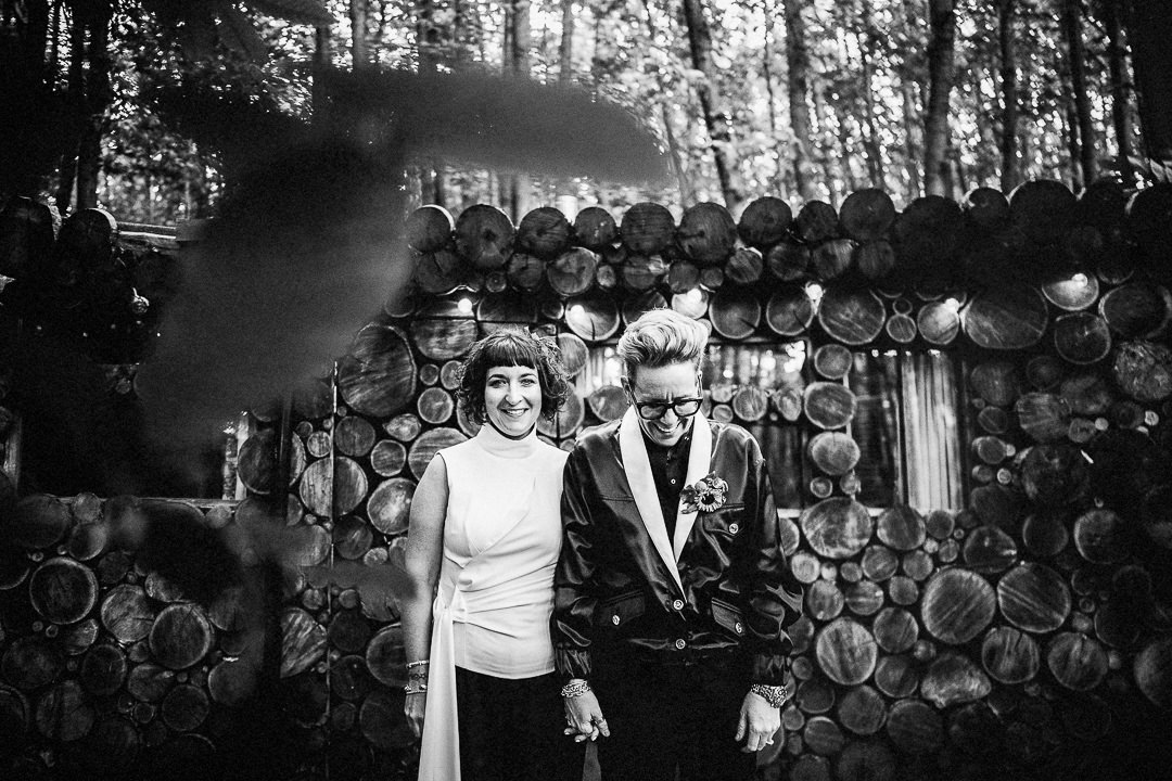 A same sex couple outside a log cabin at the dressy wedding venue