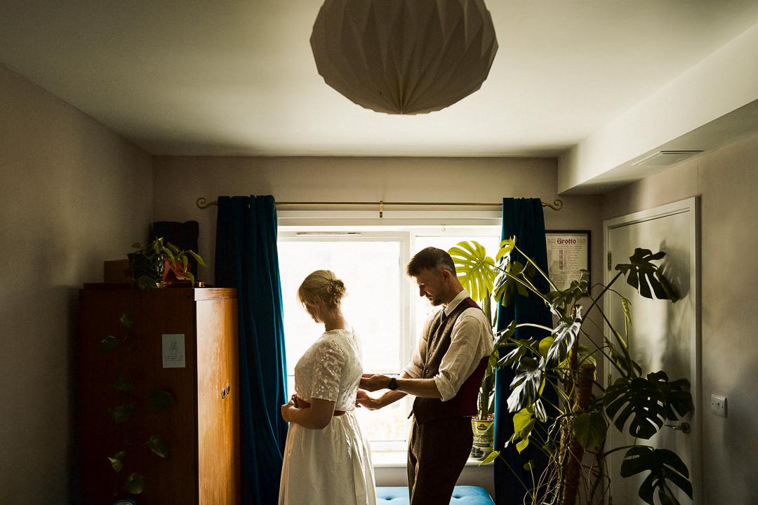 a groom helps his bride into her Wedding dress